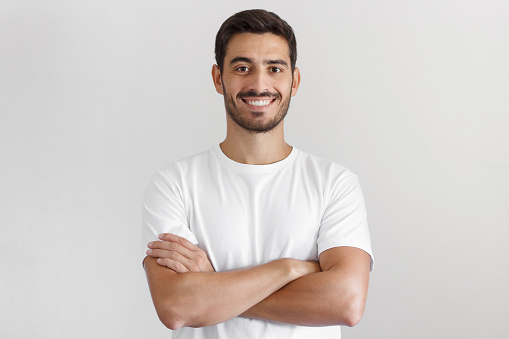 istock Portrait of smiling handsome man in white t-shirt, standing with crossed arms isolated on gray background 1025855482