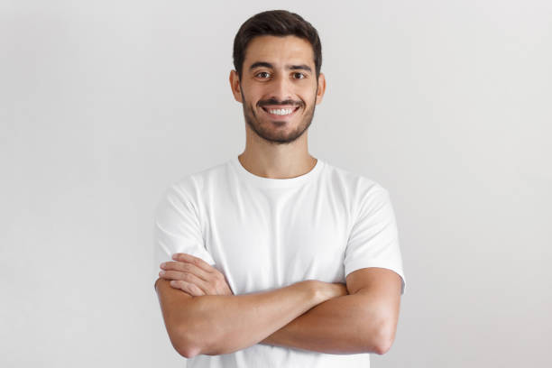 Portrait of smiling handsome man in white t-shirt, standing with crossed arms isolated on gray background Portrait of smiling handsome man in white t-shirt, standing with crossed arms isolated on gray background male likeness stock pictures, royalty-free photos & images