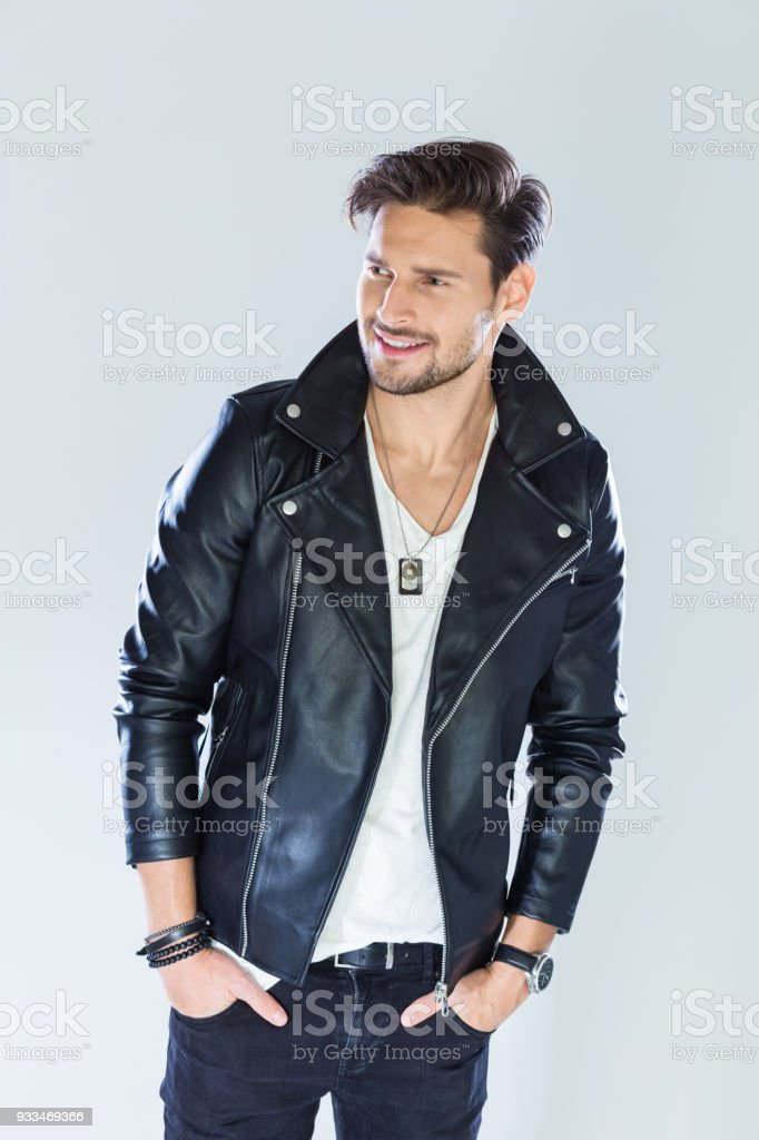 Portrait of smiling, handsome man wearing leather jacket Fashion portrait of handsome man wearing black leather jacket, looking away and smiling. Studio shot, grey background. 25-29 Years Stock Photo