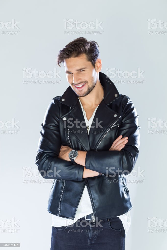 Portrait of smiling handsome man wearing leather jacket Fashion portrait of handsome man wearing black leather jacket, smiling at camera. Studio shot, grey background. 25-29 Years Stock Photo