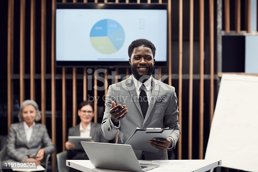 Smiling Afro-American manager presenting budget information