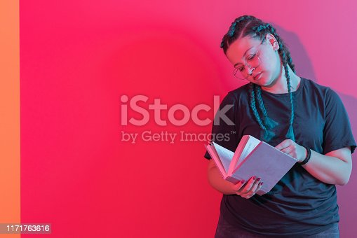 istock Portrait of smiling happy young women reading book 1171763616