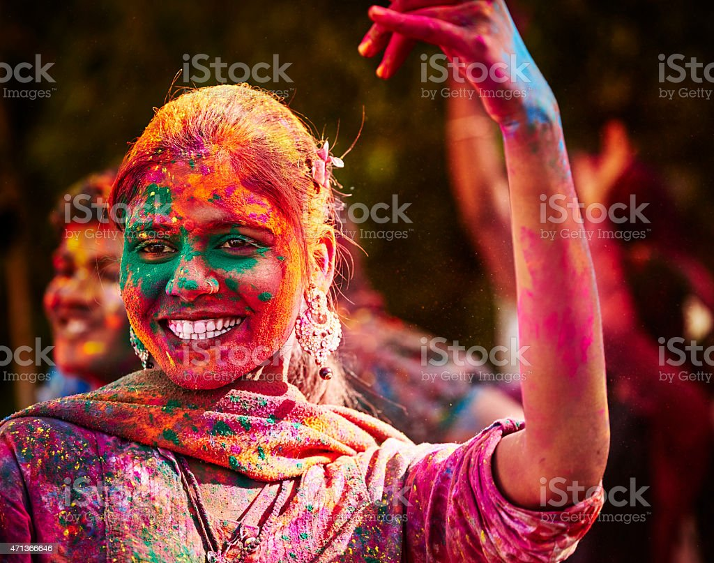 Portrait Of Smiling Indian Girl With Colored Face During Holi stock photo