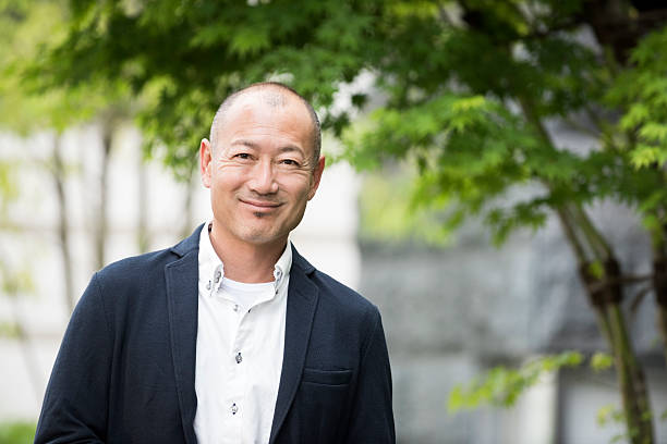 Portrait of smiling Japanese man Portrait of smiling Japanese man looking to camera. Happy Asian businessman in his 40's . only japanese stock pictures, royalty-free photos & images