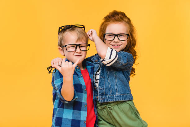 portrait of smiling kids in eyeglasses isolated on yellow - bezkręgowce zdjęcia i obrazy z banku zdjęć