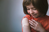 istock Portrait of smiling little child with adhesive bandage on his hand after vaccination 1316865387