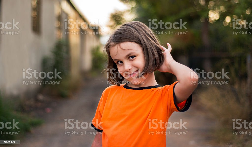 Portrait of smiling little girl looking at camera in happiness stock photo
