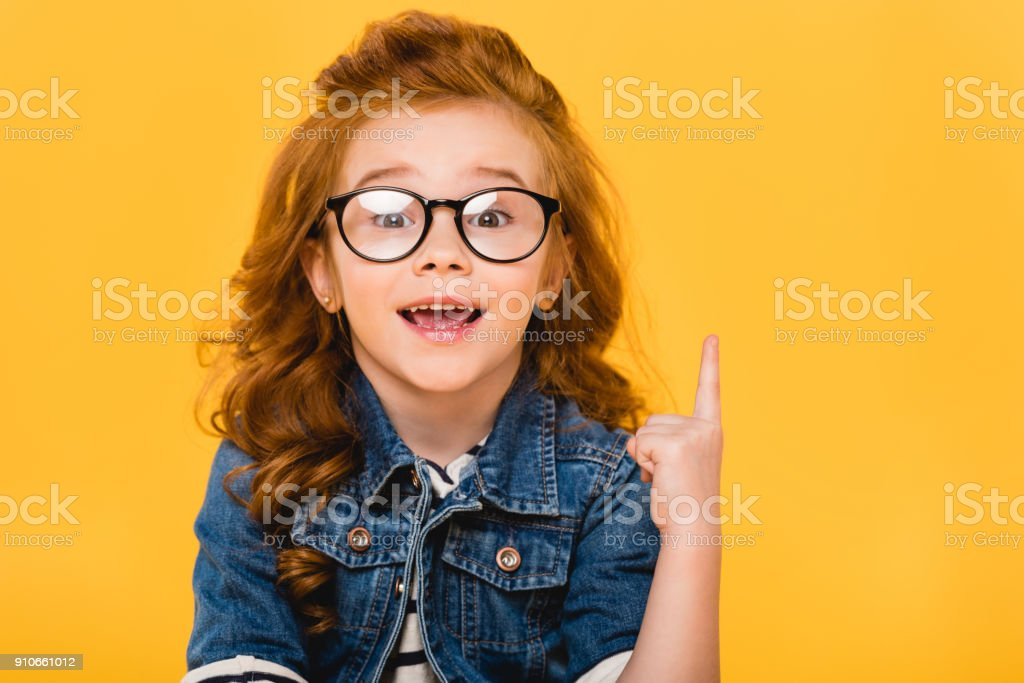 portrait of smiling little kid in eyeglasses pointing up isolated on yellow - foto stock