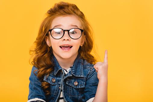 微笑的小孩子在眼鏡上的肖像 指向孤立的黃色 照片檔及更多 一個人 照片