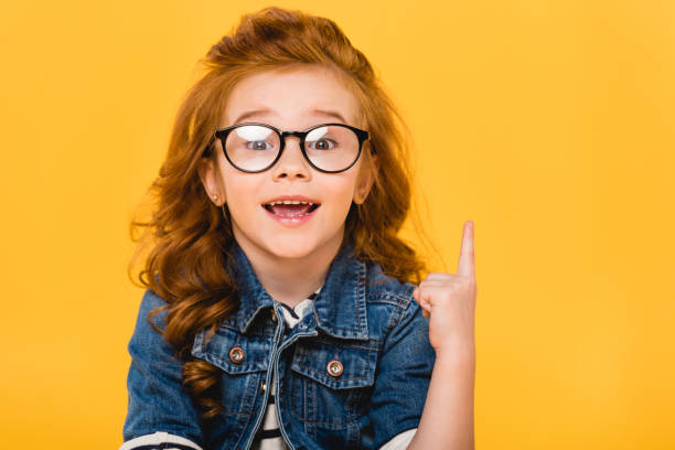 portrait of smiling little kid in eyeglasses pointing up isolated on yellow - child stock photos and pictures