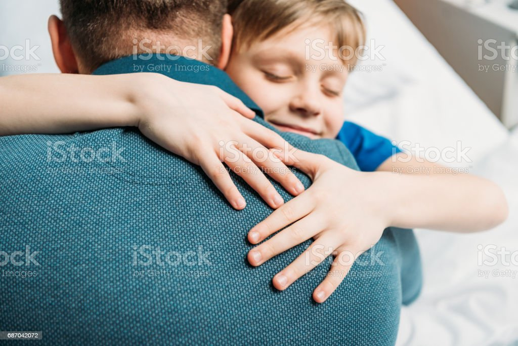 portrait of smiling little son hugging father in hospital chamber stock photo