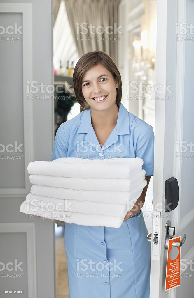 Portrait of smiling maid with towels in hotel room doorway stock photo