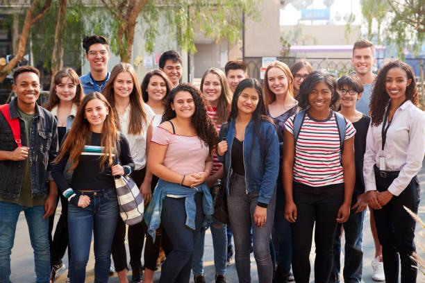retrato de sonrientes estudiantes universitarios masculinos y femeninos con maestros fuera de la escuela de construcción - estudiante fotografías e imágenes de stock