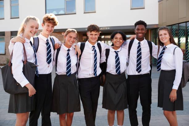 男子・女子高校生制服外の大学建物を着て笑顔の肖像画 - 制服 ストックフォトと画像