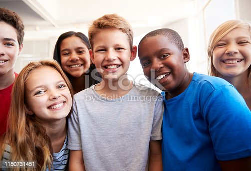 istock Portrait Of Smiling Male And Female Students In Grade School Classroom 1150731451