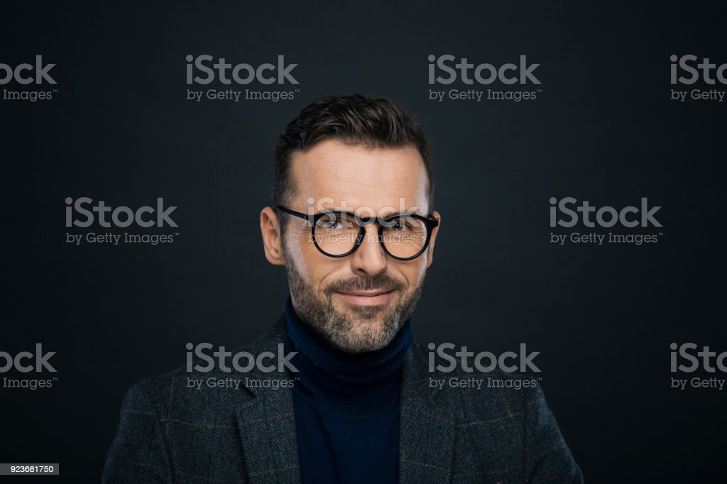 Portrait of smiling male designer, dark background Portrait of handsome businessman in tweed jacket and glasses against black background, looking at camera. 30-39 Years Stock Photo