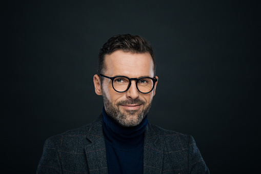 Portrait Of Smiling Male Designer Dark Background Stock Photo - Download Image Now