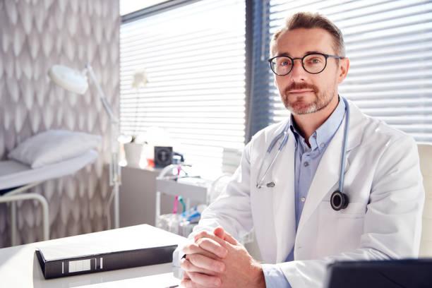 Porträt von Smiling Male Doctor Wearing White Coat mit Stethoscope Sitting Behind Desk Im Büro – Foto