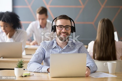 825082848istockphoto Portrait of smiling male employee in headset posing for picture 994164896