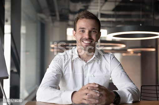 Portrait of smiling male Caucasian employee sit at office desk look at camera in modern office, happy man worker millennial businessman posing, having video call with client or customer online