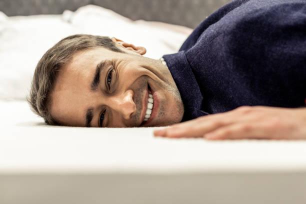 portrait de visage masculin souriant se trouvant sur des draps de lit blancs - matelas photos et images de collection