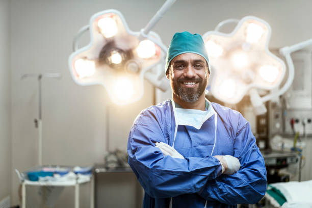 Portrait of smiling male surgeon with arms crossed stock photo