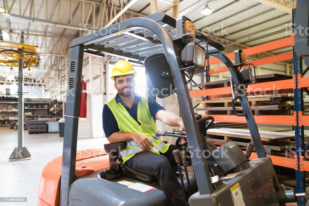 Portrait of smiling male worker on forklift Portrait of smiling young male worker sitting on forklift. Confident engineer is working in manufacturing company. He is wearing hardhat and reflective clothing. 20-24 Years Stock Photo