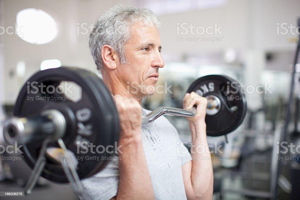 Retrato de hombre sonriente sosteniendo barra para pesas en el gimnasio - foto de stock