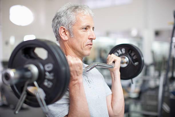 Portrait d'homme souriant tenant barre dans une salle de sport - Photo