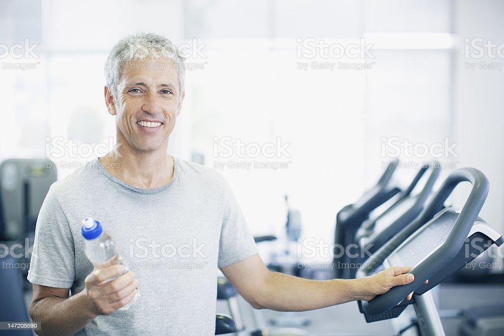 Retrato de hombre sonriente sosteniendo una botella de agua en la cinta trotadora - foto de stock