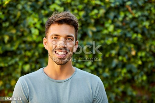 Portrait of smiling young man against plants. Confident happy male is standing in backyard. He is wearing blue t-shirt.