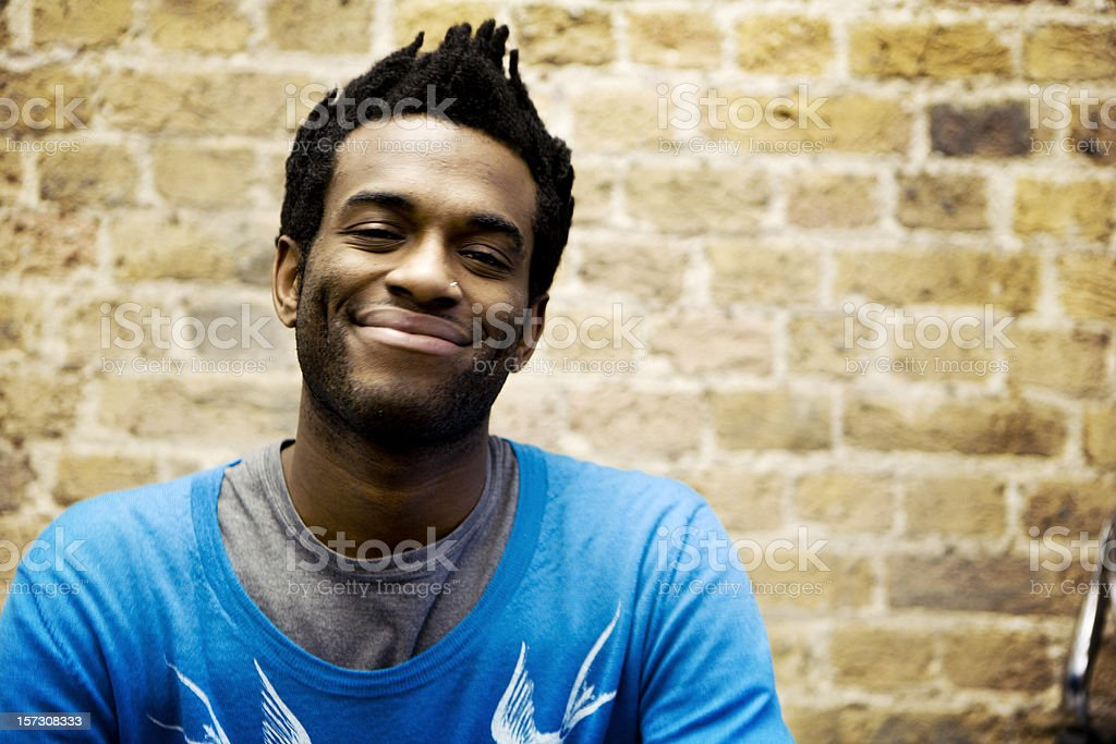 Portrait of smiling man in front of brick wall. stock photo