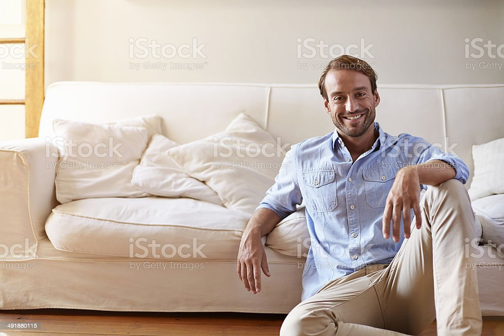 Portrait of smiling man leaning against sofa stock photo