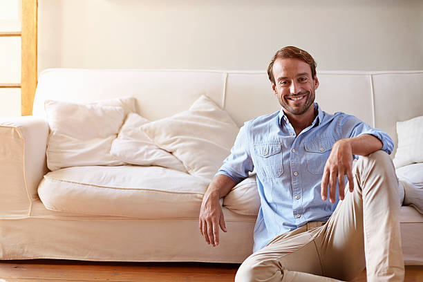 portrait of smiling man leaning against sofa - sitting on floor stock photos and pictures