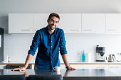 Portrait of smiling mid adult man leaning on kitchen island. Confident handsome male is standing in domestic kitchen. He is wearing casuals at home.