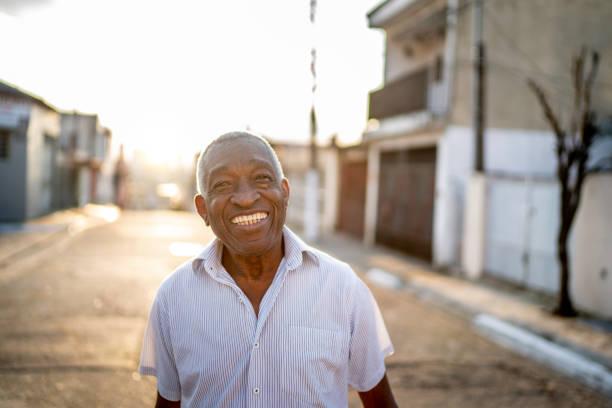 porträt eines lächelnden mannes, der auf der straße in die kamera schaut - einzelner senior stock-fotos und bilder