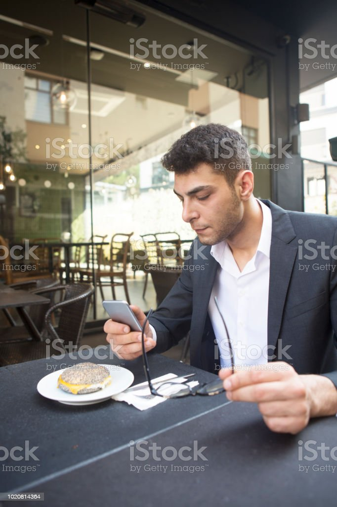 Portrait of smiling man looking at smartphone at the cafe. stock photo
