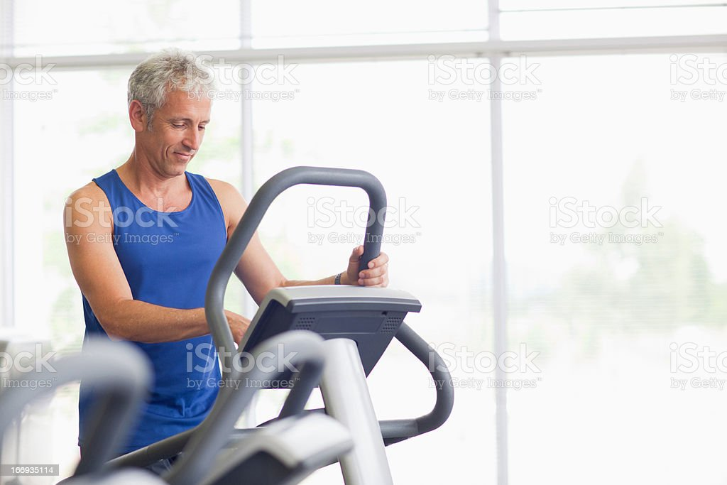 Retrato de hombre sonriendo en máquina elíptica en el gimnasio - foto de stock