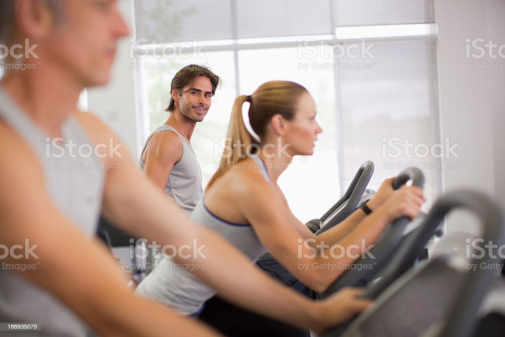Portrait of smiling man on exercise bike in gymnasium royalty-free stock photo