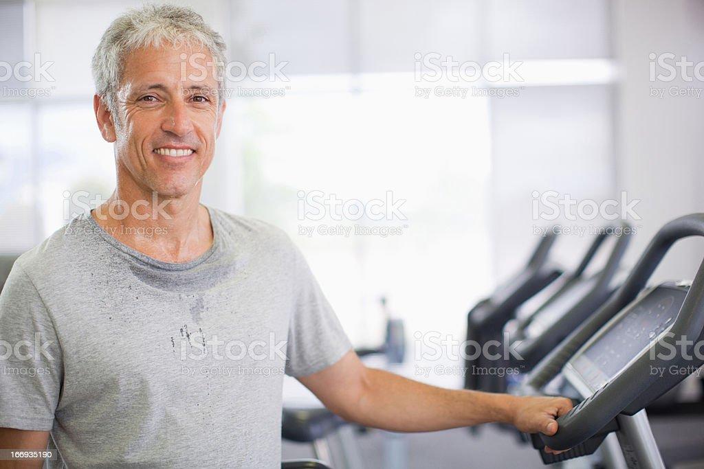 Retrato de la sonriente hombre en la máquina trotadora del gimnasio - foto de stock
