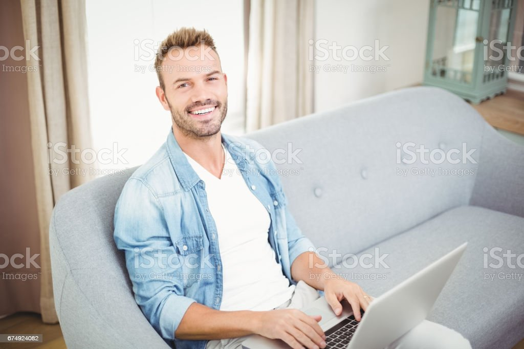 Portrait of smiling man using laptop at home royalty-free stock photo