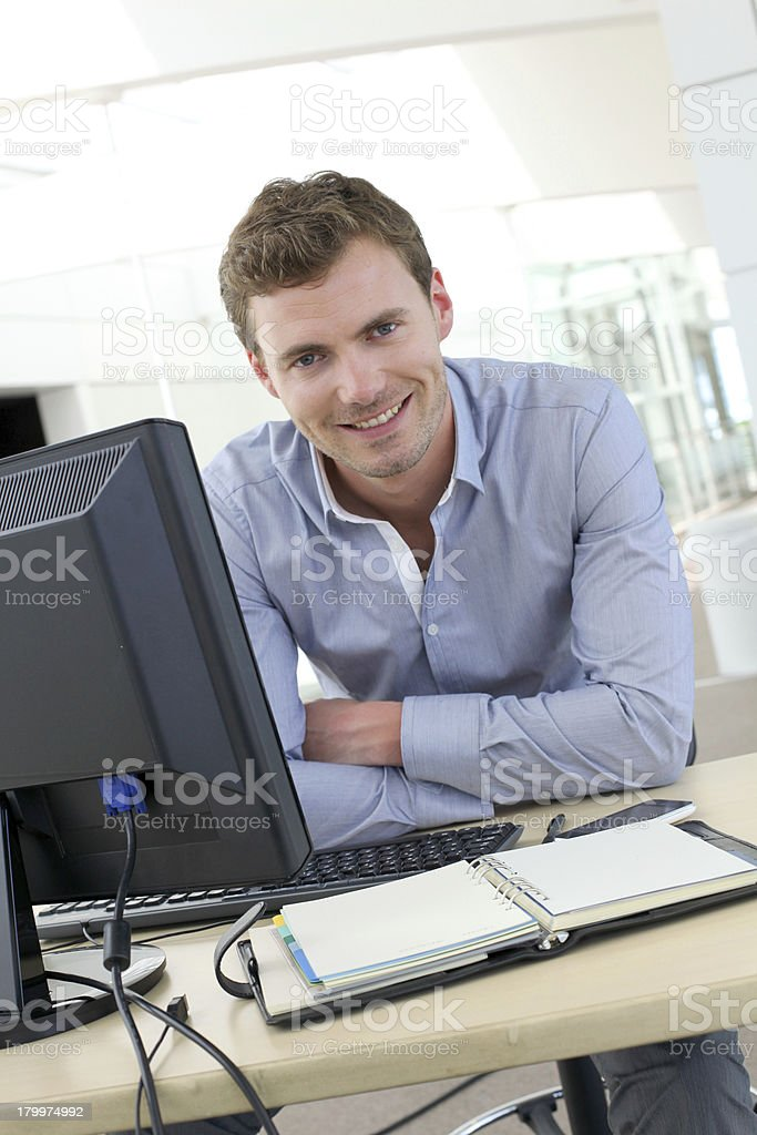 Portrait of  smiling man with arms crossed sitting at desk royalty-free stock photo