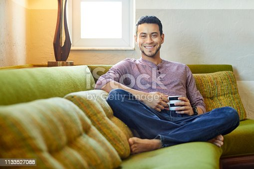 Portrait of confident smiling young man holding coffee cup on sofa. Handsome male is sitting in living room. He is in casuals at home.