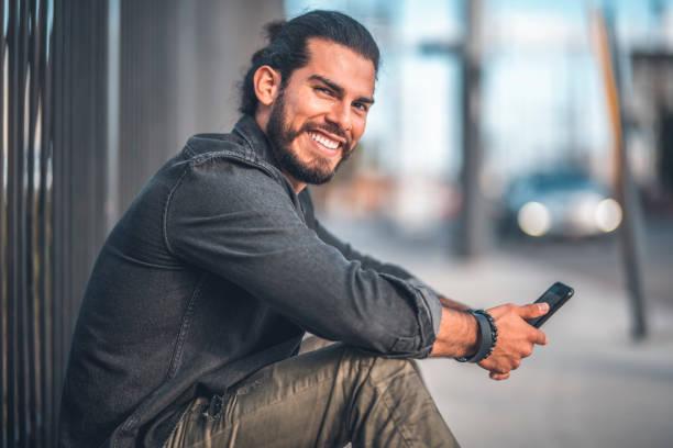 Porträt von lächelnden Mann mit Handy in Stadt – Foto
