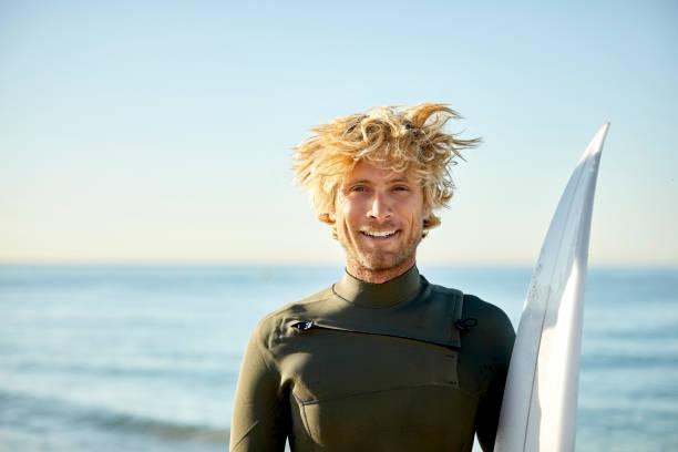 Porträt eines lächelnden Mannes mit Surfbrett gegen Meer – Foto