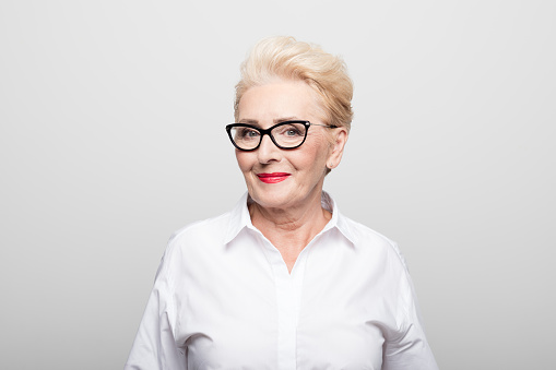Portrait of senior female manager smiling. Close-up of beautiful professional is against white background. She is wearing eyeglasses.