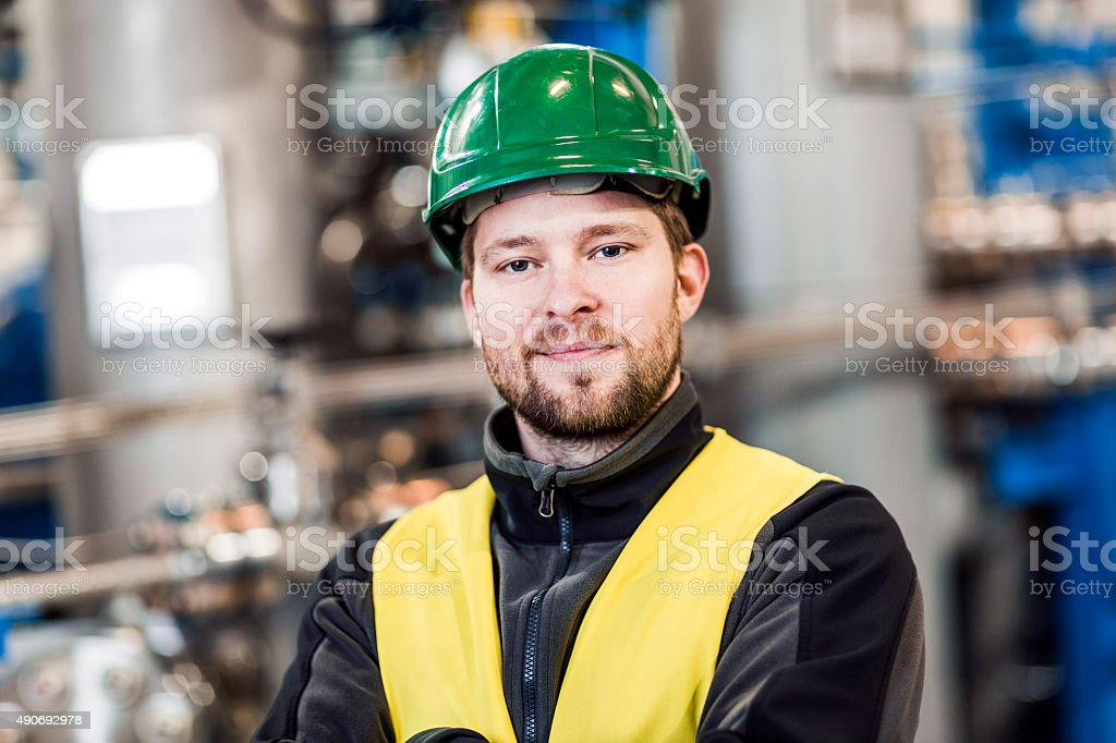 Portrait of smiling manual worker at factory stock photo