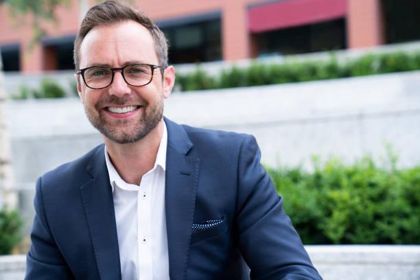 Porträt eines lächelnden, reifen Geschäftsmannes, der vor dem Bürogebäude sitzt – Foto