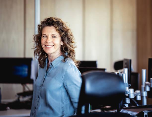 portrait de la souriante femme mature au bureau - une seule femme senior photos et images de collection