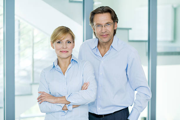 Portrait of smiling, mature, confident business partners in blue shirts stock photo